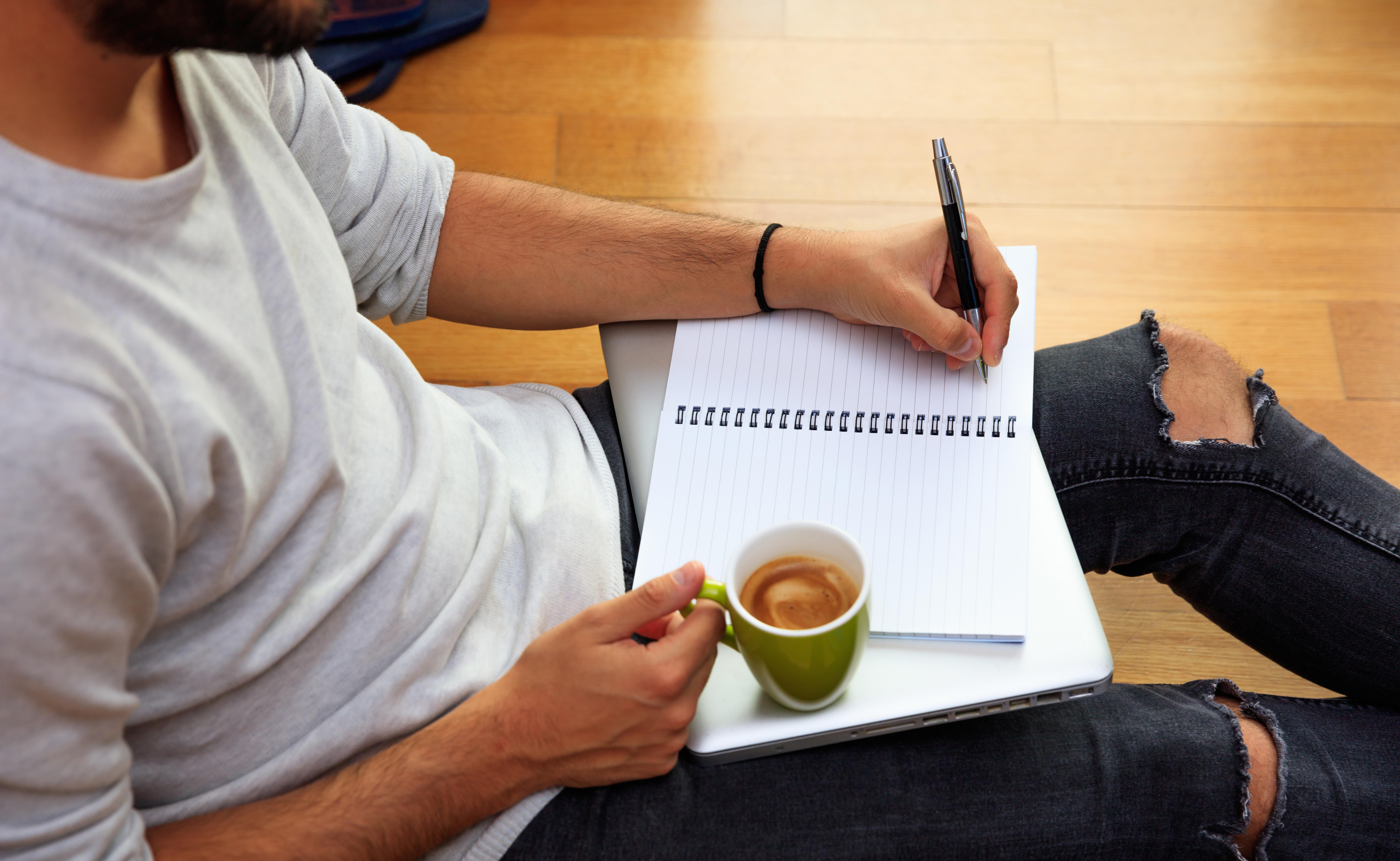 left-handed-man-writing-sitting-on-the-floor-PVJJME5.jpg